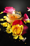Candle and Roses. A candle  glowing on the water along with beautiful yellow rose and pink petals Stock Images