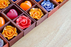 Candle roses and candle hearts in wooden box Royalty Free Stock Photos