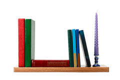 Candle and several books are on the shelf. Objects is on a white background Stock Photo