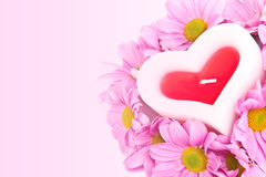 Candle in the shape of a heart and chrysanthemums. Stock Photos