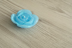 Candle in the shape of a rose. On a wooden background Royalty Free Stock Image