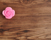 Candle in the shape of a rose. On a wooden background Royalty Free Stock Photo