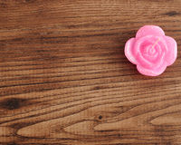 Candle in the shape of a rose. On a wooden background Royalty Free Stock Photography