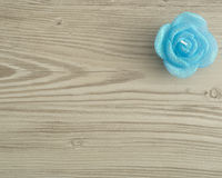 Candle in the shape of a rose. On a wooden background Royalty Free Stock Images
