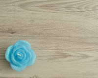 Candle in the shape of a rose. On a wooden background Stock Photo
