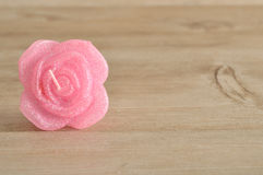 Candle in the shape of a rose. On a wooden background Royalty Free Stock Photos
