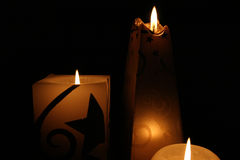 Candle Shapes. Multiple candles glowing brightly in a shadowed grouping of shapes including circle, square and oblesque Stock Images