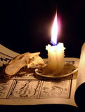 Candle and Skull. A burning candle and unidentified animal skull sitting on a page illustrating 19th Century tarot cards stock photo