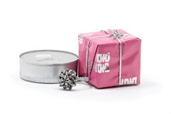 Candle with small present and ring. Over white stock photos
