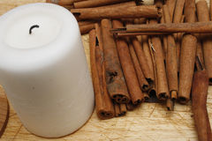 Candle. Small white pillar candle with cinnamon sticks Stock Photography