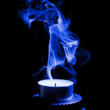 Candle with smoke. Extinguished candle with blue smoke on black background Royalty Free Stock Photos
