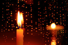 Candle stands in front of a window with rain drops. Royalty Free Stock Photo