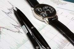 Candle stick chart and watch, pen. Stock Images
