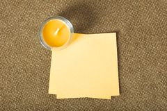 Candle and sticky notes on fabric background Royalty Free Stock Images