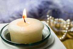 Candle Still Life. A still Life of a small candle in a glass container with pearls in the background Royalty Free Stock Images