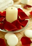 Candle, stones and petals of roses. Stock Photo
