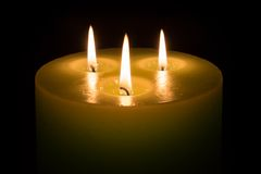 Candle with three flames on black background Stock Images