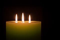 Candle with three flames on black background Stock Photography