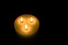 Candle with three flames on black background Royalty Free Stock Images