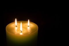 Candle with three flames on black background Royalty Free Stock Image