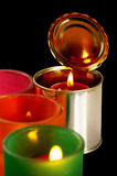 Candle on a tin can. Red candle on a tin can over black background Royalty Free Stock Photo