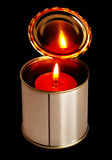 Candle on a tin can. Over black background Royalty Free Stock Photos