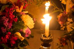 Candle and tomb with flowers at cemetery stock image