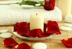 Candle, towel and petals of red rose. Royalty Free Stock Photography