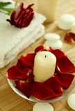 Candle, towel and petals of red rose Royalty Free Stock Image