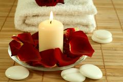 Candle, towel and petals of red rose. Stock Images