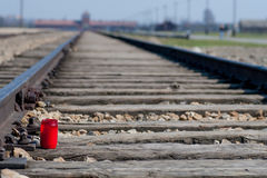 Candle on a train track in Auschwitz. Birkenau with Main Entrance in the background. Oswiecim, Poland Royalty Free Stock Image