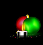 Candle and two Christmas ball. Black background and burning candle with two Christmas ball Royalty Free Stock Photos