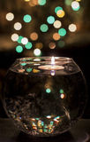 Candle in a vase. With water against garland sparks Stock Images