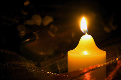 Candle and violin. Candle in the darkness, set against a background of a violin and various Christmas decorations Stock Photography