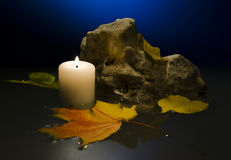 Candle in water. Burning candle in water, on water autumn leaves of a maple and a birch, on a background a comment and a dark blue background swim royalty free stock photography