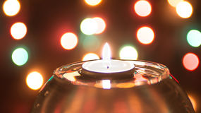 Candle in the water on the background of garlands. Christmas Eve. Dark. Stock Photography