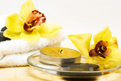 Candle in water with orchids royalty free stock photography