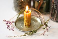 Candle of wax, made by hand, with magic herbs stock photos