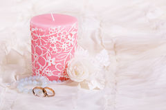 Candle and wedding rings. Light composition with candle and two wedding rings. Copy space stock images