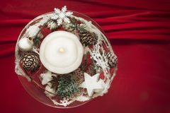 Candle with winter decoration on red silk Royalty Free Stock Photos
