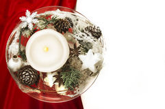 Candle with winter decoration on red silk and white background Royalty Free Stock Image