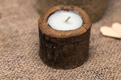 Candle in a wooden candlestick on a romantic background Royalty Free Stock Image