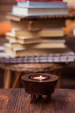 Candle on wooden table with books in background Royalty Free Stock Photography