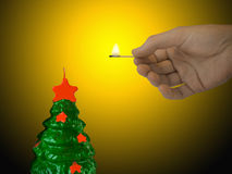 Candle (xmas tree). And hand with match Stock Photography