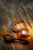 Candle in yellow glass candlestick with air bubbles inside, incense stick Smoking , fish oil capsules Royalty Free Stock Image