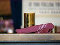 Candleholder and utensils wrapped in purple napkin sitting on a restaurant table stock images