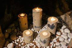 Candleholders that look like birch logs holding replaceable tealight candles and sitting on a bed of decorative stones in a firepl Stock Photo