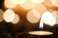 Candlelight against bokeh background. Blue candle flame against defocused golden candlelight background Stock Image