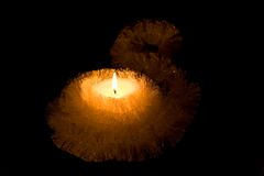 Candlelight Candle. Christmas Candle. Small candle with bright glowing flames on a black background Stock Photos
