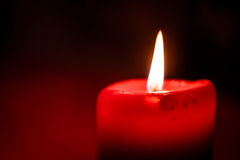Candlelight. Close-up photo of a flaming red candlelight at christmas time royalty free stock image